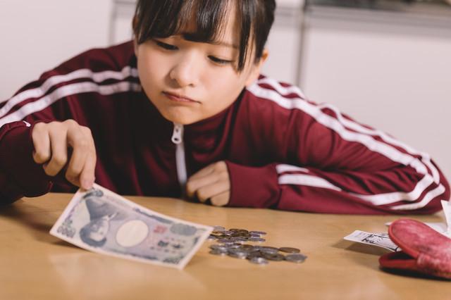 千円札を手にする女性