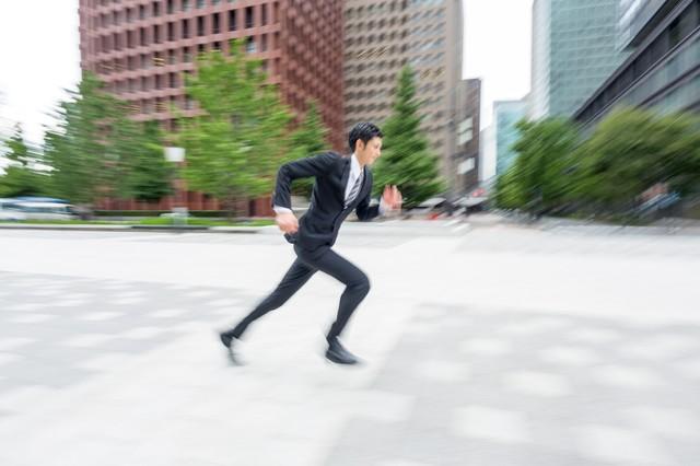 ビジネス街を走るビジネスマン