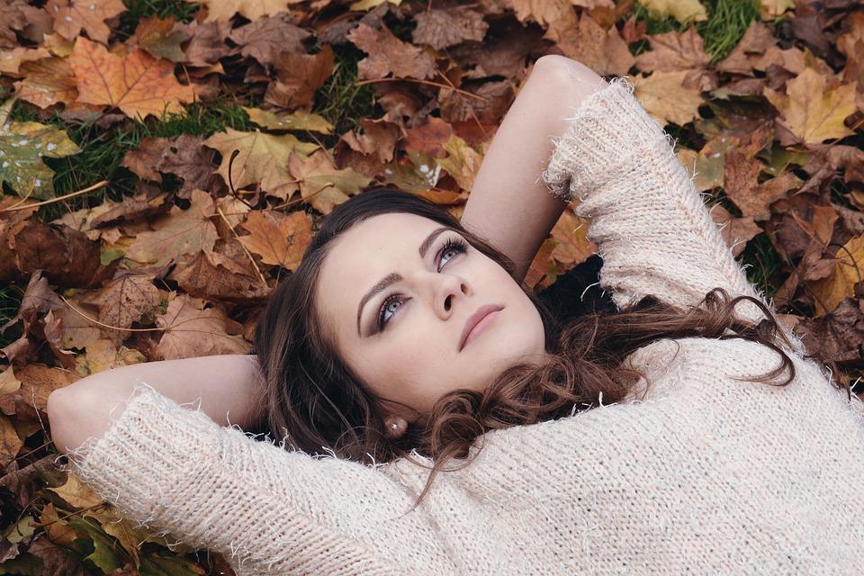 落ち葉の上で寝転ぶ女性